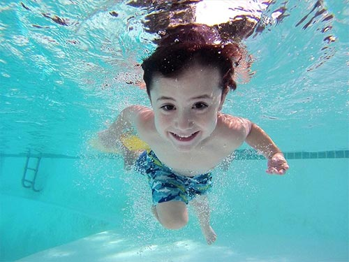 young boy underneath the surface of a home pool